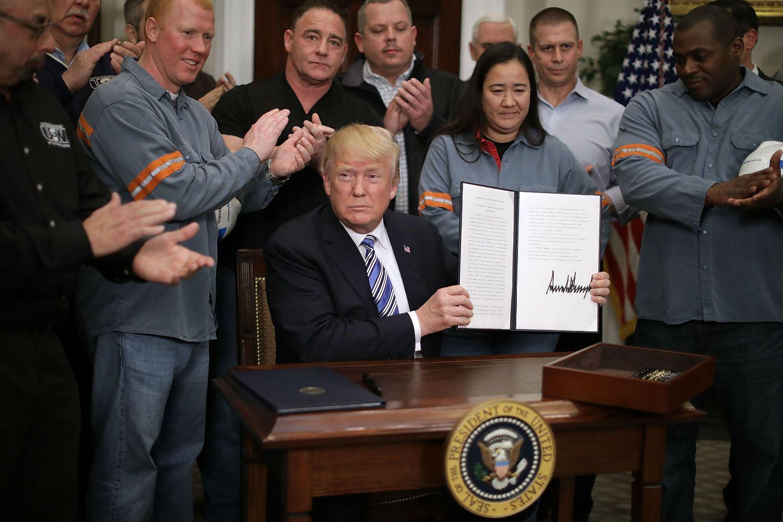Trump firmando ley de aranceles al aluminio y acero.
